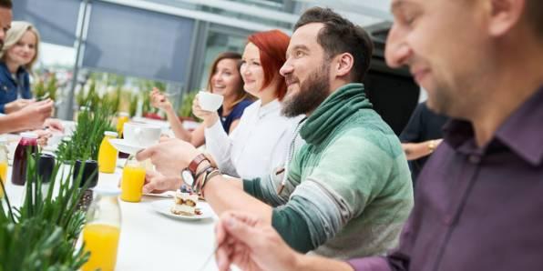 Pracownicy lidla wspólnie siedzą przy posiłku w miłej atmosferze.