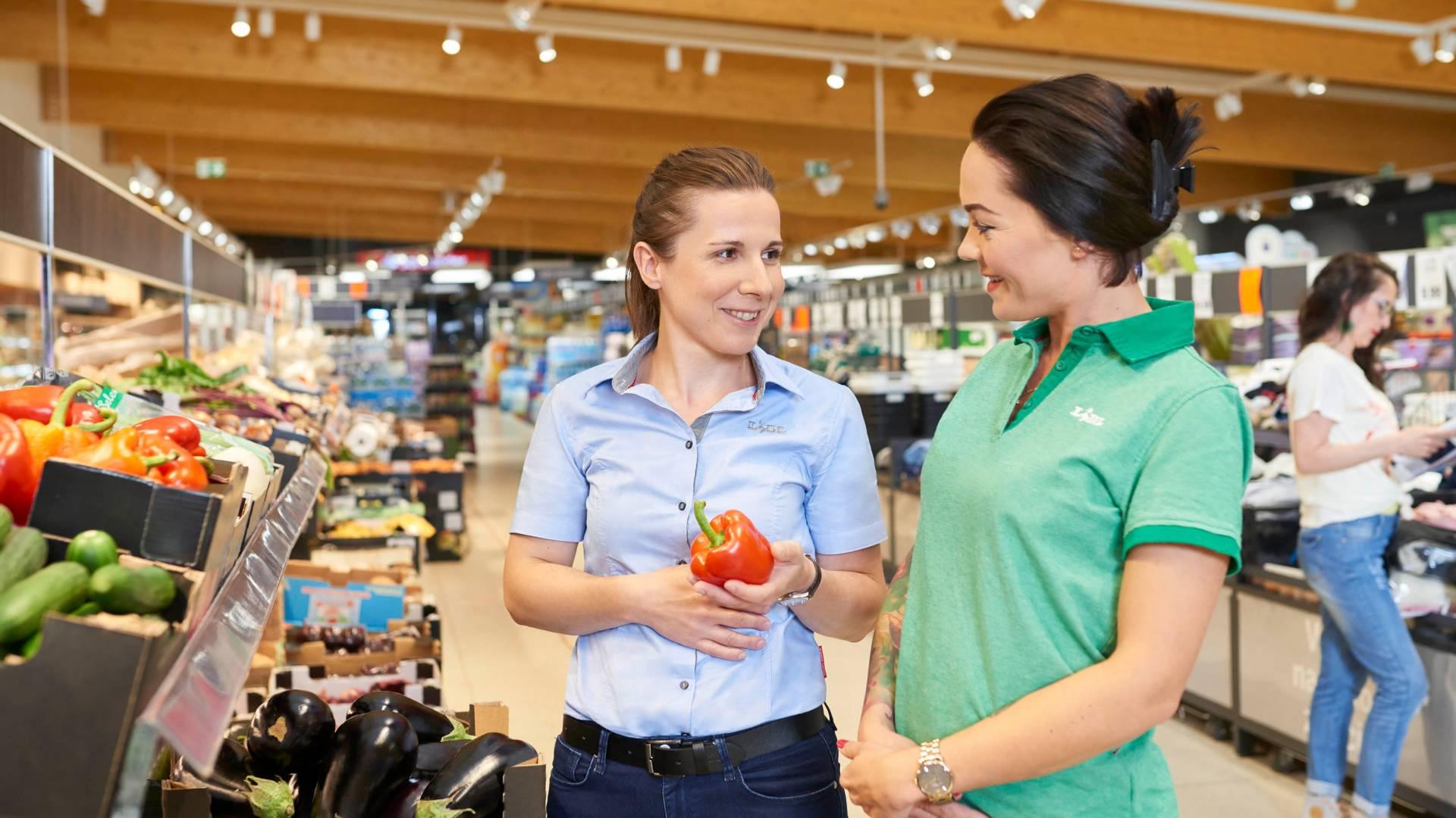 Praca w sklepie lidla. Pracownicy sklepu stoją przy półce z warzywami i sprawdzają jakość produktów.