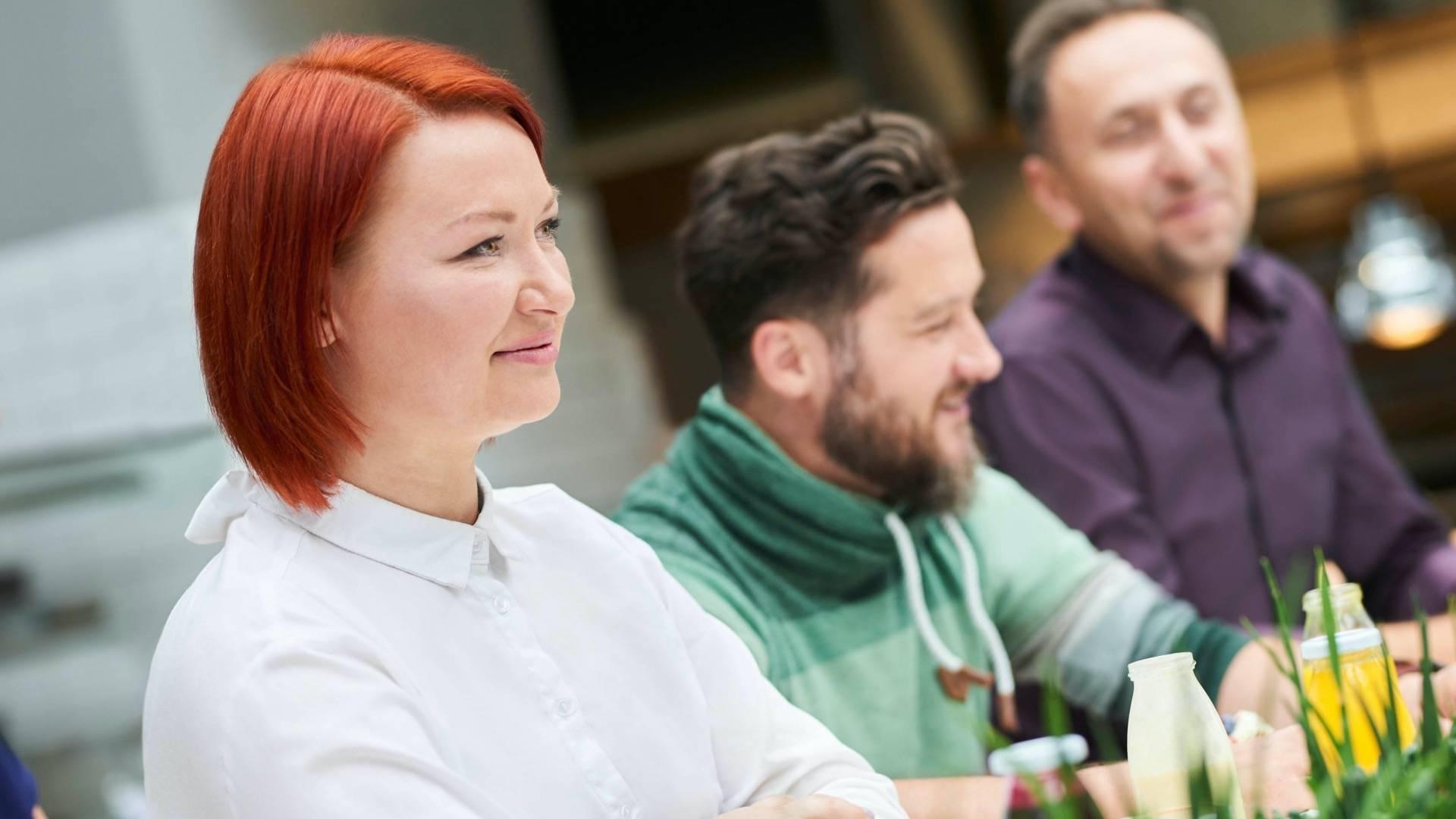 Poznaj Lidla jako pracodawcę. Kobiety i mężczyźni, pracownicy Lidla, siedzą przy stole i rozmawiają w miłej atmosferze.