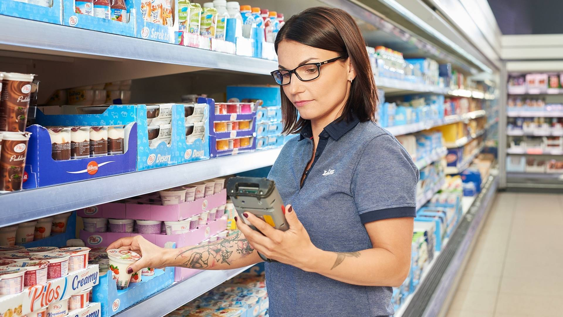 Praca w sklepie. Kobieta pracownik sklepu stoi przy lodówce z nabiałem i sprawdza jakość produktów.