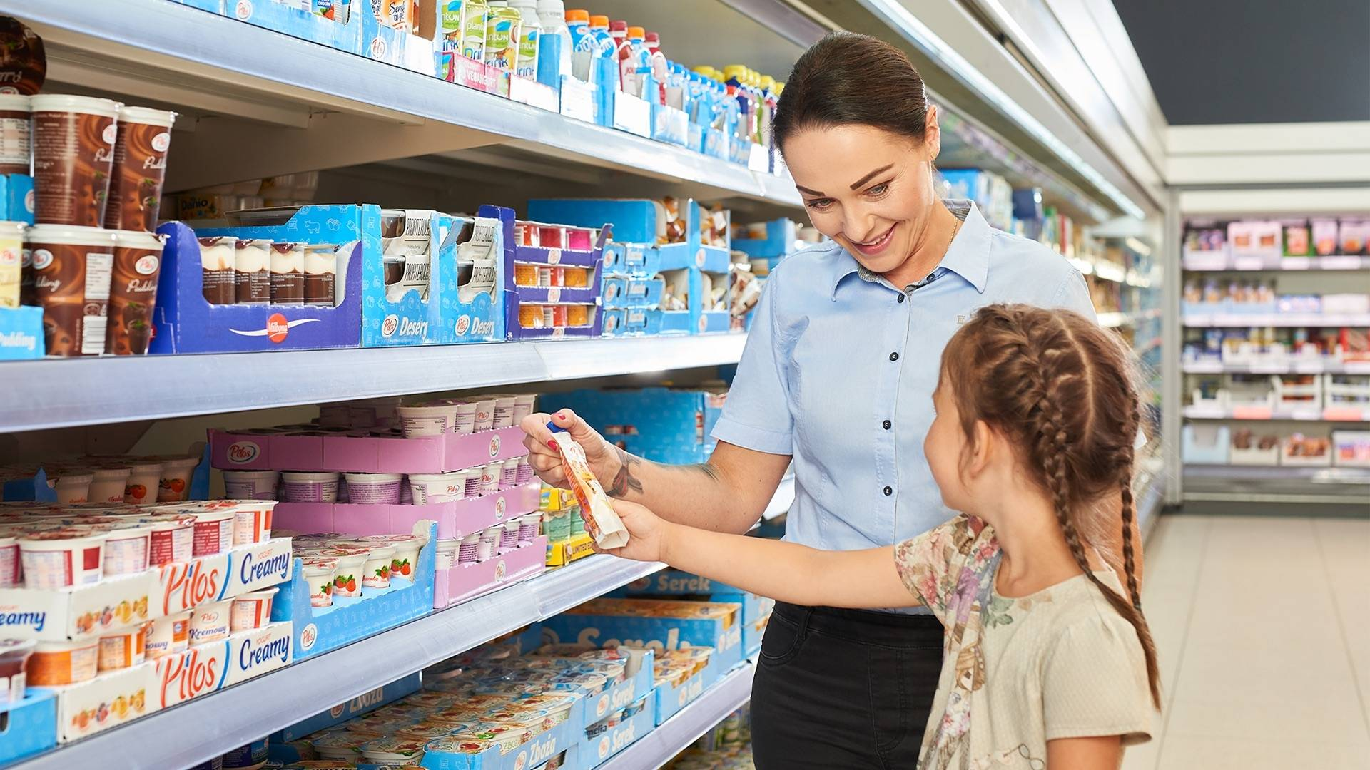 Praca w sklepie. Zastępca managera sklepu podaje produk klientowi - dziecku.