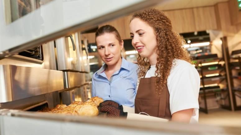 Manager sklepu pomaga pracownikowi sklepu przy odpieku pieczywa