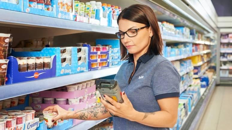 Pracownik sklepu sprawdza datę przydatności produktów