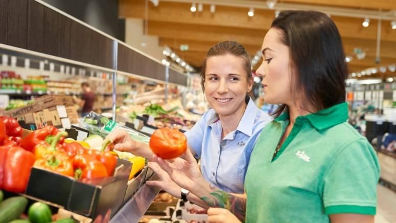 Manager sklepu rozmawia z pracownikiem sklepu przy stoisku z warzywami