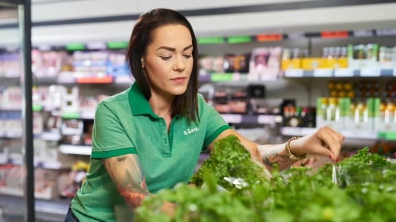 Pracownik sklepu wykłada towar i poprawia eskpozycję warzyw na półce