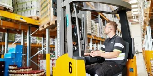 Pracaw magazynie. Pracownik magazynuprzy pomocy wózka widłowego zdejmuje palatę produków z regału.
